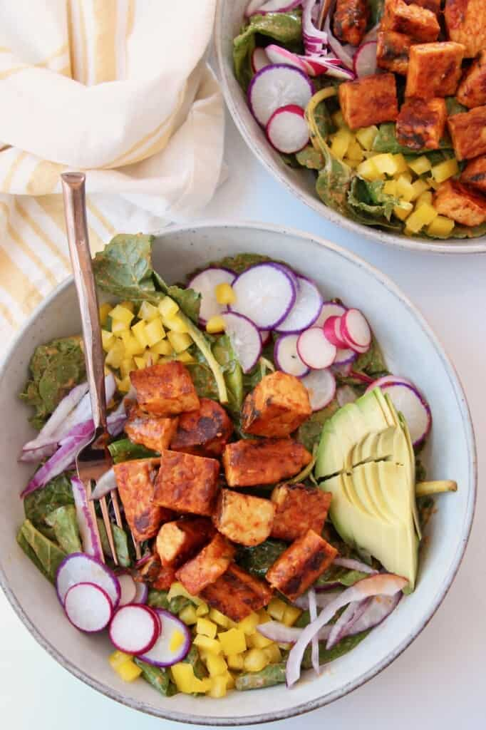 buffalo tempeh cubes on top of salad in bowl with fork