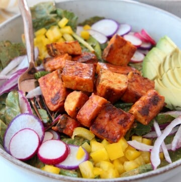 cubes of buffalo tempeh on salad in a bowl