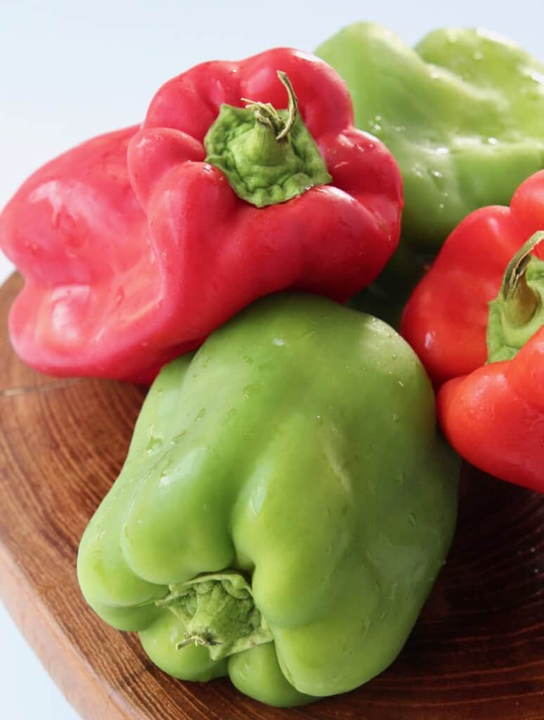 bell peppers stacked up on wood cutting board