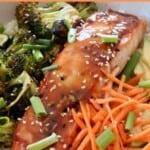teriyaki glazed salmon in bowl with shredded carrots and roasted broccoli