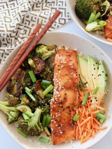 teriyaki salmon in bowl with sliced avocado and roasted vegetables
