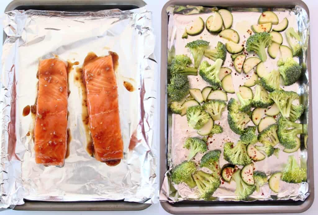 salmon on foil lined baking sheet, next to veggies on foil lined baking sheet