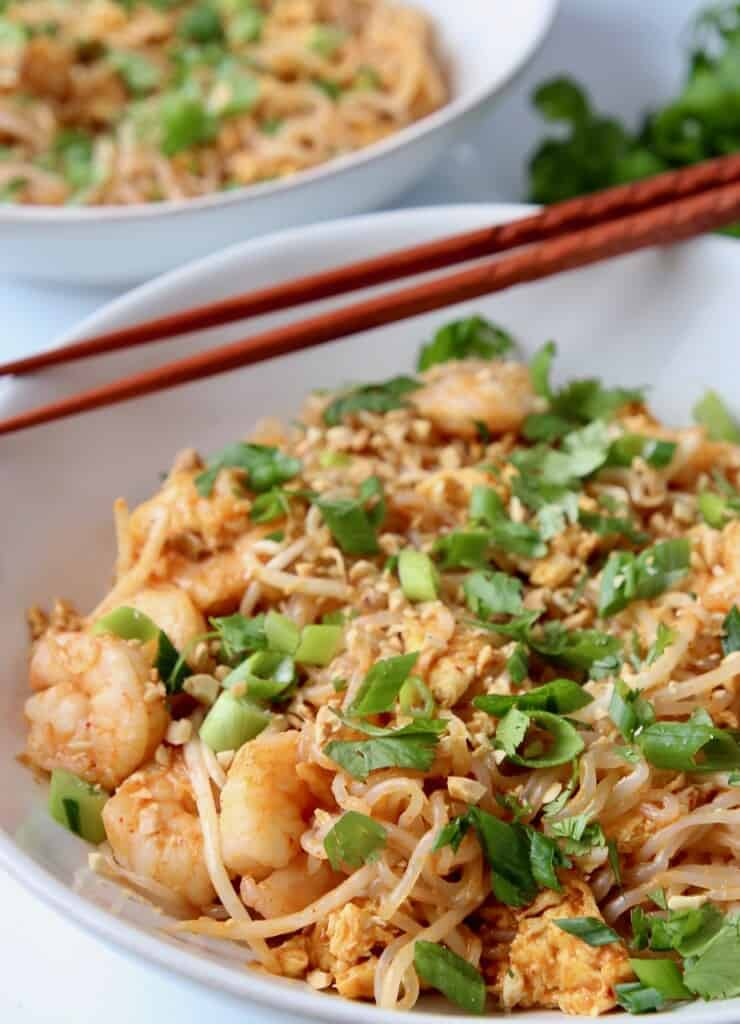 pad thai with shrimp in bowl with chopsticks on the side