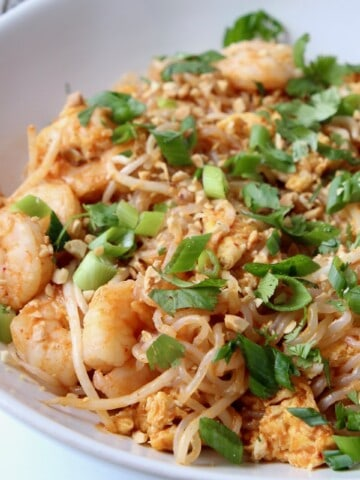shrimp pad thai in white bowl topped with green onions