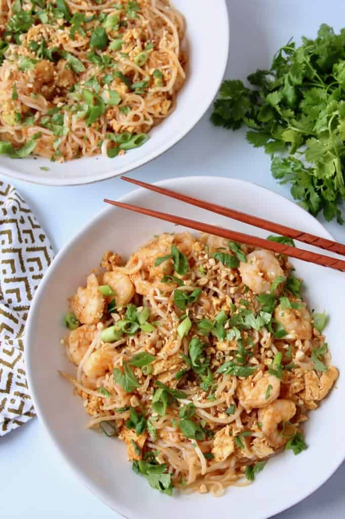 shrimp pad thai in bowl with chopsticks and cilantro on the side