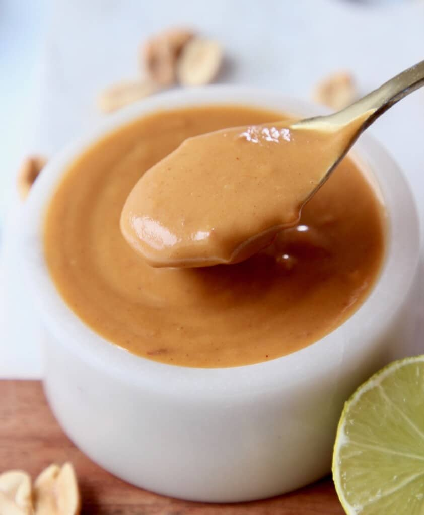 creamy peanut sauce in bowl with spoon lifting sauce out of the bowl