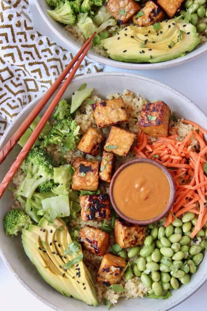 bowl filled with vegetables, cooked tempeh and a small bowl of peanut sauce