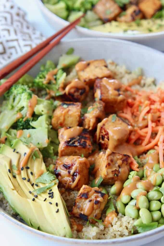 cooked tempeh in bowl topped with peanut sauce with vegetables on the side