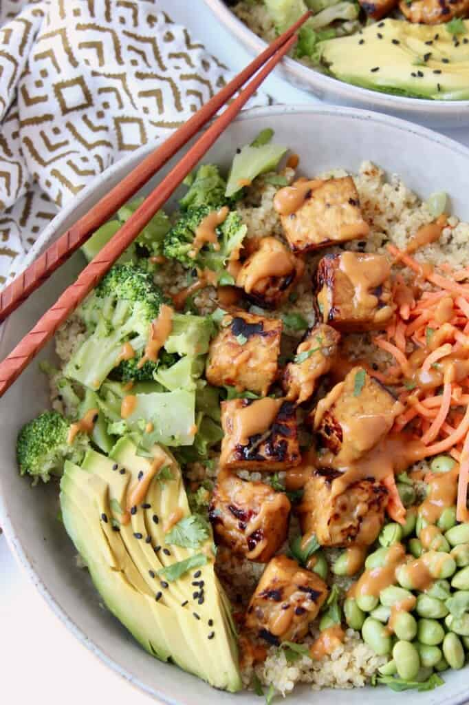 cooked tempeh cubes in bowl with vegetables and chopsticks on the side