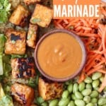 cooked cubes of tempeh in bowl with peanut sauce and vegetables