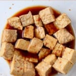 cubes of tempeh in Asian style marinade in glass bowl