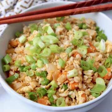 fried rice in white bowl with chopsticks on the side